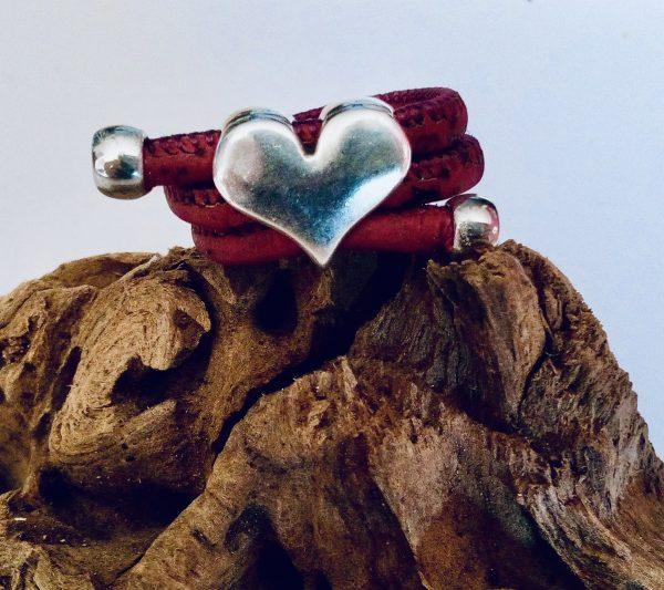 Naturfarbener Korkring mit silbernem Herz auf einem Stück Holz