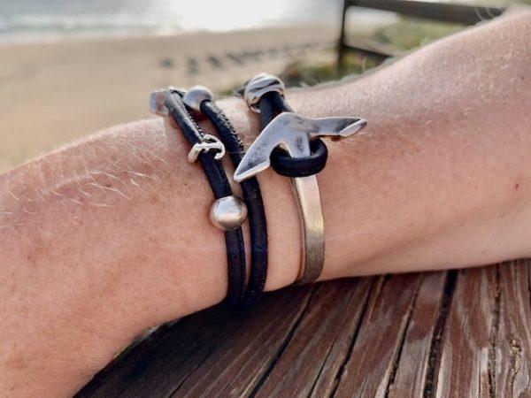 Schwarzes Armband mit Ankerverschluss mit sonnigem Strand im Hintergrund