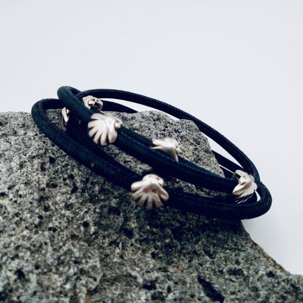 Dunkelblaues Armband mit Silber Muscheln auf hellem Hintergrund