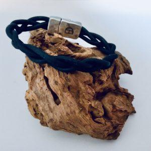 Geflochtenes Korkarmband auf einem Stück Holz in Dunkelblau