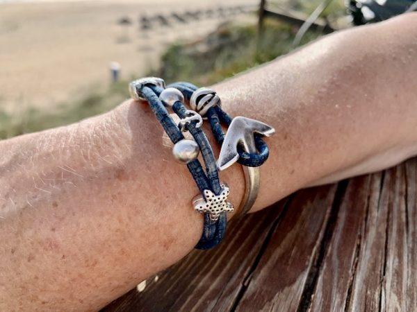 Jeansblaues Armband mit Ankerverschluss mit sonnigem Strand im Hintergrund