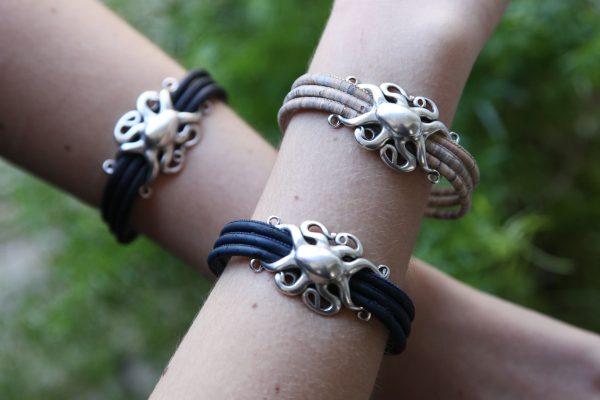 Verschiedenfarbige Armbänder mit silbernem Oktopus am Arm getragen in natürlicher Umgebung
