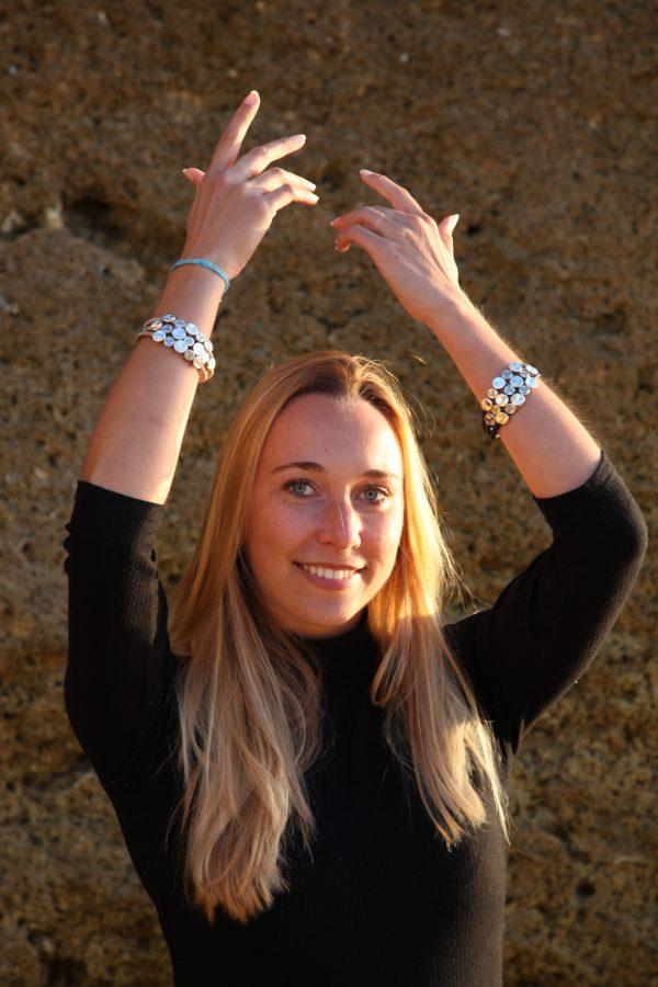 Model mit Silberplättchen Armband am Strand in der Sonne