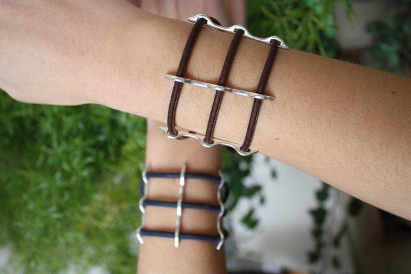 Braunes Korkarmband mit Silbersteg getragen vor einem natürlichem Hintergrund