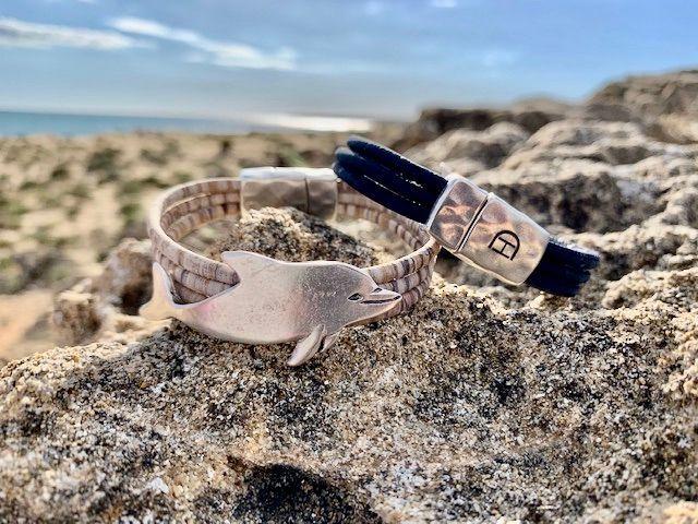 Zwei Armbänder mit Delfin auf hellen Steinen am Strand