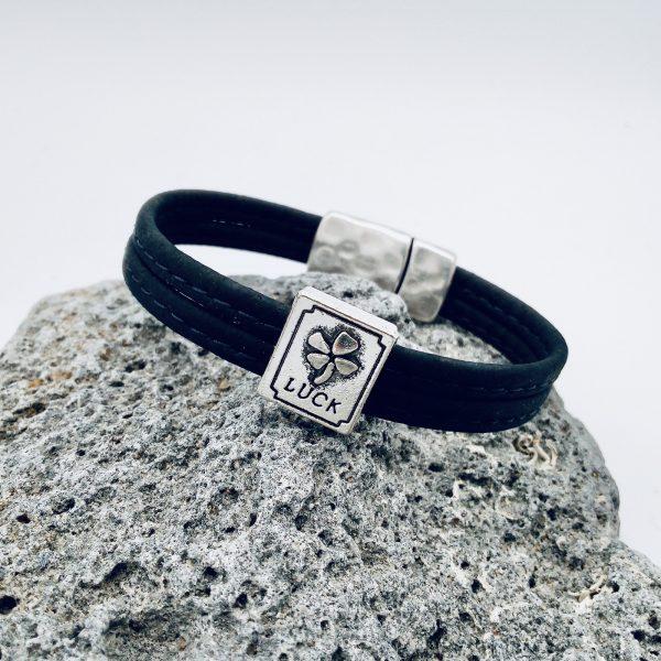 """Schwarzes """"Lucky"""" Armband auf grauem Stein"""