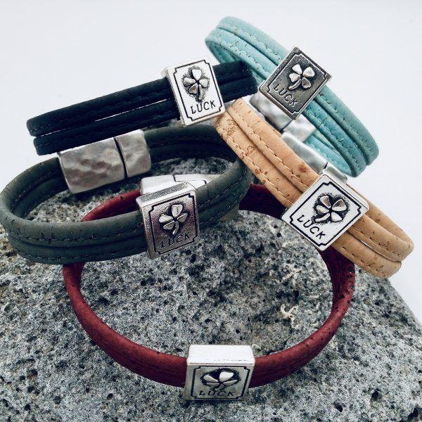 Lucky Armbänder in verschiedenen Farben auf grauem Vulkanstein