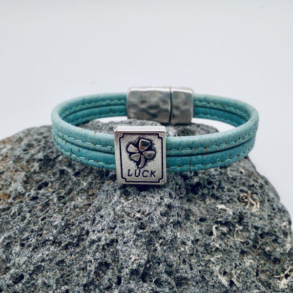 """Hellblaues """"Lucky"""" Armband auf grauem Stein"""