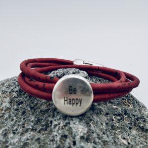 "Rotes ""Be Happy "" Armband auf hellem Vulkanstein"
