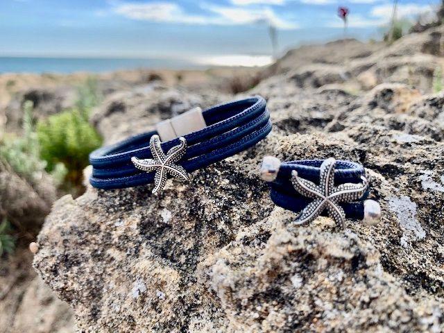 Armband und Ring mit silbernem Seestern auf Steinen in der Sonne am Strand